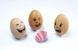 Egg faces and an easter egg Stock Photography