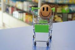 Egg feliz la sonrisa dentro de una mini carretilla con el fondo borroso del interior de la tienda Conceptual Fotografía de archivo libre de regalías