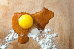 Egg and flour on a cutting board Stock Images
