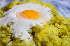 Egg on the flour and grated potatoes Royalty Free Stock Photo