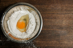 Egg and flour in plate on wooden table Stock Image