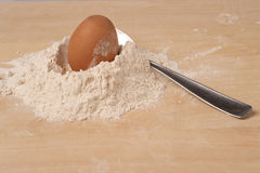Egg flour and spoon. An egg some flour and a spoon on a wooden background Royalty Free Stock Images
