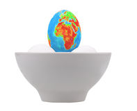 Egg in the form of globe in white cup. Stock Photo