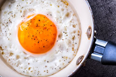 Egg. Fried egg. Chicken egg. Close up view of the fried egg on a frying pan. Salted and spiced fried egg Royalty Free Stock Photo