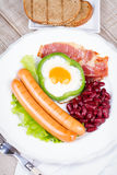 Egg fried in green pepper, sausages, bacon and red beans Stock Images
