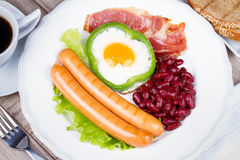 Egg fried in green pepper, sausages, bacon and red beans Royalty Free Stock Image