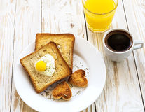 Egg fried in a heart-shaped toast cutout sprinkled Stock Photography