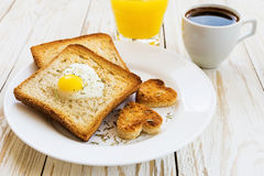 Egg fried in a heart-shaped toast cutout sprinkled Stock Image