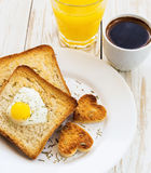 Egg fried in a heart-shaped toast cutout sprinkled Royalty Free Stock Photography