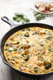 Egg frittata baked in cast iron skillet with a plate of potatoes Royalty Free Stock Images