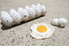 Egg fry on sidewalk illustrated. Fried egg with broken shells and carton of white eggs with illustrated faces on hot sidewalk on summer day Royalty Free Stock Photo