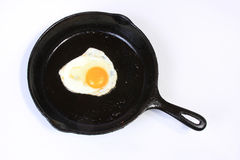 Egg in the Frying Pan. One egg in a black skillet frying pan on a white background Stock Photos