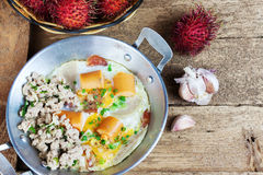 Egg frying pan and Rambutan fruit. Indochina pan-fried egg with pork and sausage toppings on wood table. Rambutan fruit Stock Photography