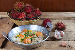 Egg frying pan and Rambutan fruit. Indochina pan-fried egg with pork and sausage toppings on wood table. Rambutan fruit Royalty Free Stock Image