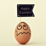 egg with a funny face with a signboard with the text happy easter royalty free stock photography