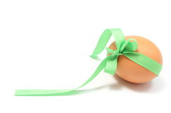 Egg with green ribbon and copy space for text. White background Stock Photos