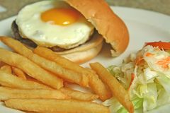 Egg Hamburger. An enticing shot of hamburger with egg,fries and coleslaw stock images