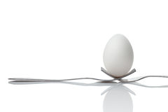 Hold the world in your hands. An egg hanging by two forks Royalty Free Stock Photo