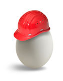 Egg with hardhat. Egg with red hardhat in light back Royalty Free Stock Photo