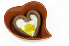 Egg with a heart-shaped sausages in red heart-shaped plate Stock Image