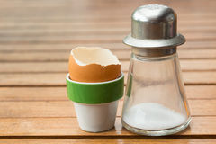 Egg holder and salt shaker with an eaten egg. Royalty Free Stock Photography
