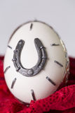 Egg with horseshoes. On red lace Royalty Free Stock Images