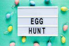 Egg hunt text on lightbox on green pastel paper background with yellow, pink, blue eggs Bright template for Easter, top view, royalty free stock photos
