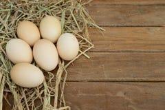Egg im Heunest auf hölzernem Tabellenhintergrund stockfoto
