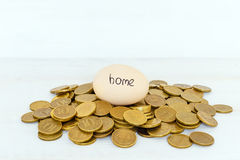 An egg with the inscription `home` lies on coins on a white background Stock Photography