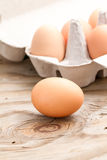 Egg. Isolated chicken egg, on wood with eggs in carton. Eggs are on a wooden background,eggs, egg, white, isolated, tray, brown, chicken, breakfast Royalty Free Stock Images