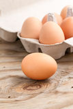 Egg. Isolated raw egg on wooden background with eggs in a carton as a background Stock Images