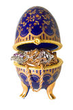 Egg with jewelry. Gold ornaments are photographed in a casket in the form of egg Royalty Free Stock Photography