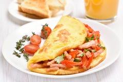 Egg l'omelette con le verdure ed il prosciutto sul piatto bianco Immagini Stock