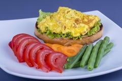 Egg l'omelette sur un morceau de pain frit avec les haricots verts, la tomate rouge et la carotte d'un plat, fin  Concept de déje Photographie stock libre de droits