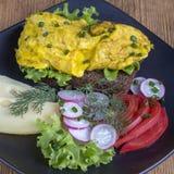 Egg l'omelette sur un morceau de pain noir avec les tomates, le fromage et le radis rouges sur une table en bois, fin  Photos libres de droits