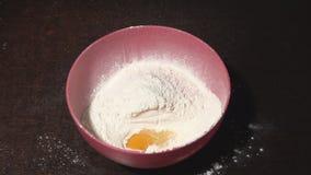 Egg la chute dans un bol de farine banque de vidéos