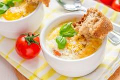 Egg le cocotte en ramekin blanc avec la tomate et le basilic photo stock