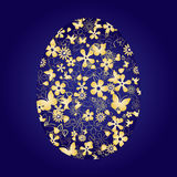 Egg made from gold things on blue background royalty free stock photos