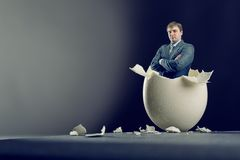 Egg with man inside isolated on gray background Royalty Free Stock Photos
