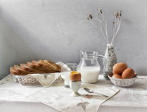 Egg and milk Still Life. Still Life milk in transparent glass jar, glass, purified egg on a stand with a spoon, napkin with shells, bread, wicker ware and bottle royalty free stock photo