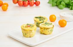 Egg muffins, paleo, keto diet. Omelet with spinach, vegetables, tomatoes baked in small molds.  royalty free stock photo