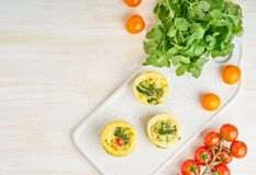 Egg muffins, paleo, keto diet. Omelet with spinach, vegetables, tomatoes baked in small molds, top view, copy space.  stock image