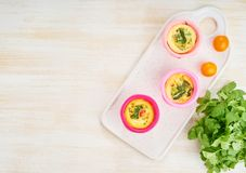 Egg muffins, paleo, keto diet. Omelet with spinach, vegetables, tomatoes in small molds, copy space.  royalty free stock image