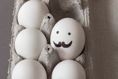 Egg with mustaches and eyes. Carton of raw white chicken eggs royalty free stock photo