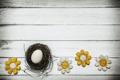 Egg in nest with flowers around on wooden background Stock Photo