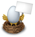 Egg In a Nest Holding a Blank Sign Royalty Free Stock Photos