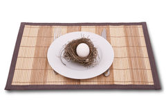 Egg in a nest served on a plate. Chicken egg in a nest served on a plate Stock Photos