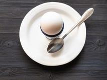 Egg no copo e na colher na placa branca na tabela escura imagem de stock royalty free