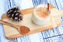 Egg Nog drink and spoon and pine cone Stock Photography