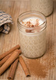 Egg nog in a mason jar. Egg nog in small half pint mason jar.  Cinnamon sticks and cinnamon are scattered on a wooden base Royalty Free Stock Photography